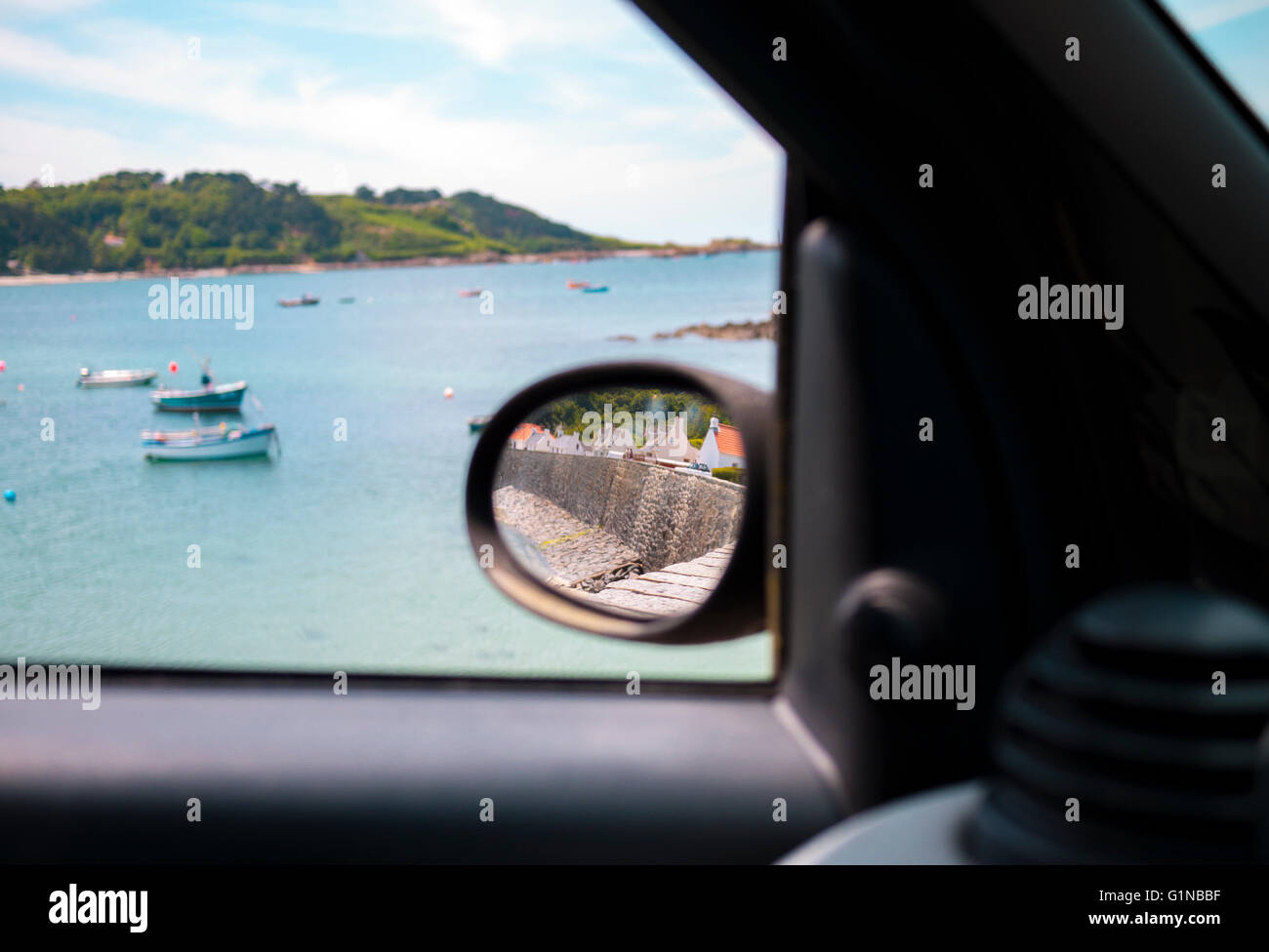 Unique view out a car window of a picturesque beach with fishing boats in Guernsey, Channel Island. - Stock Image