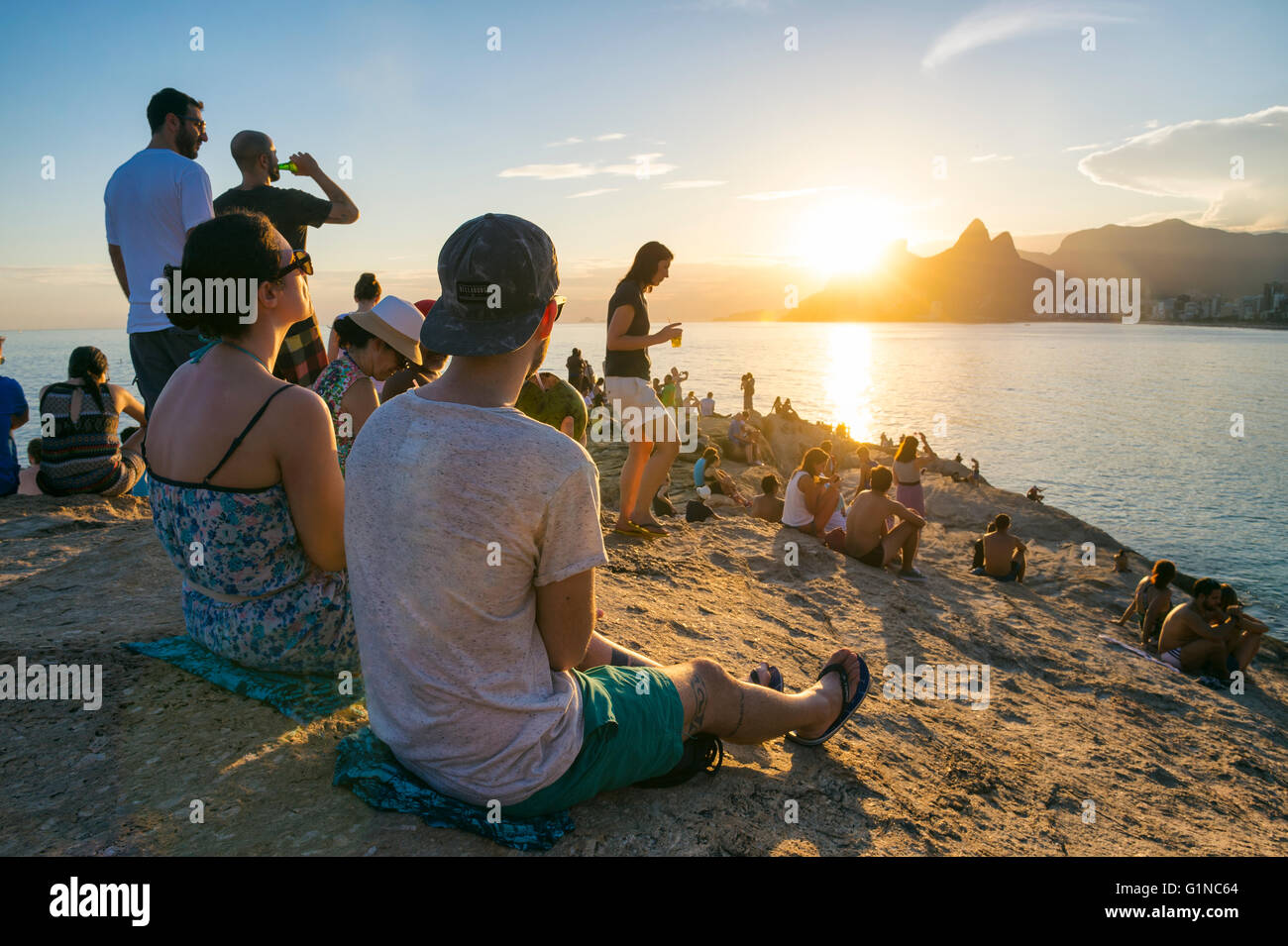 RIO DE JANEIRO - FEBRUARY 26, 2016: Crowds of people gather to watch the sunset on the rocks at Arpoador, a popular - Stock Image