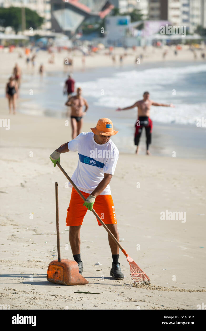 RIO DE JANEIRO - APRIL 3, 2016: Worker from the municipal COMLURB maintenance company rakes the sand on Copacabana - Stock Image