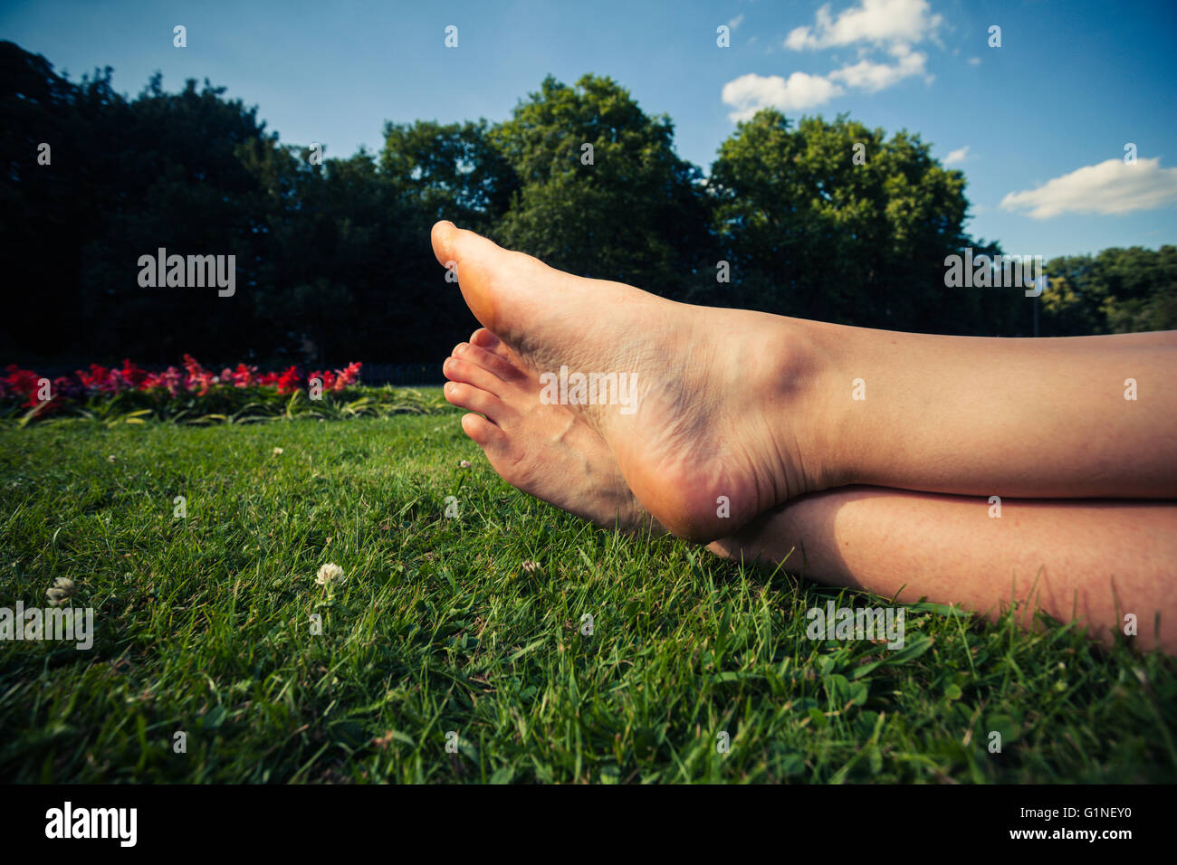 The feet of a young woman lying in the grass in a park on a summer day - Stock Image