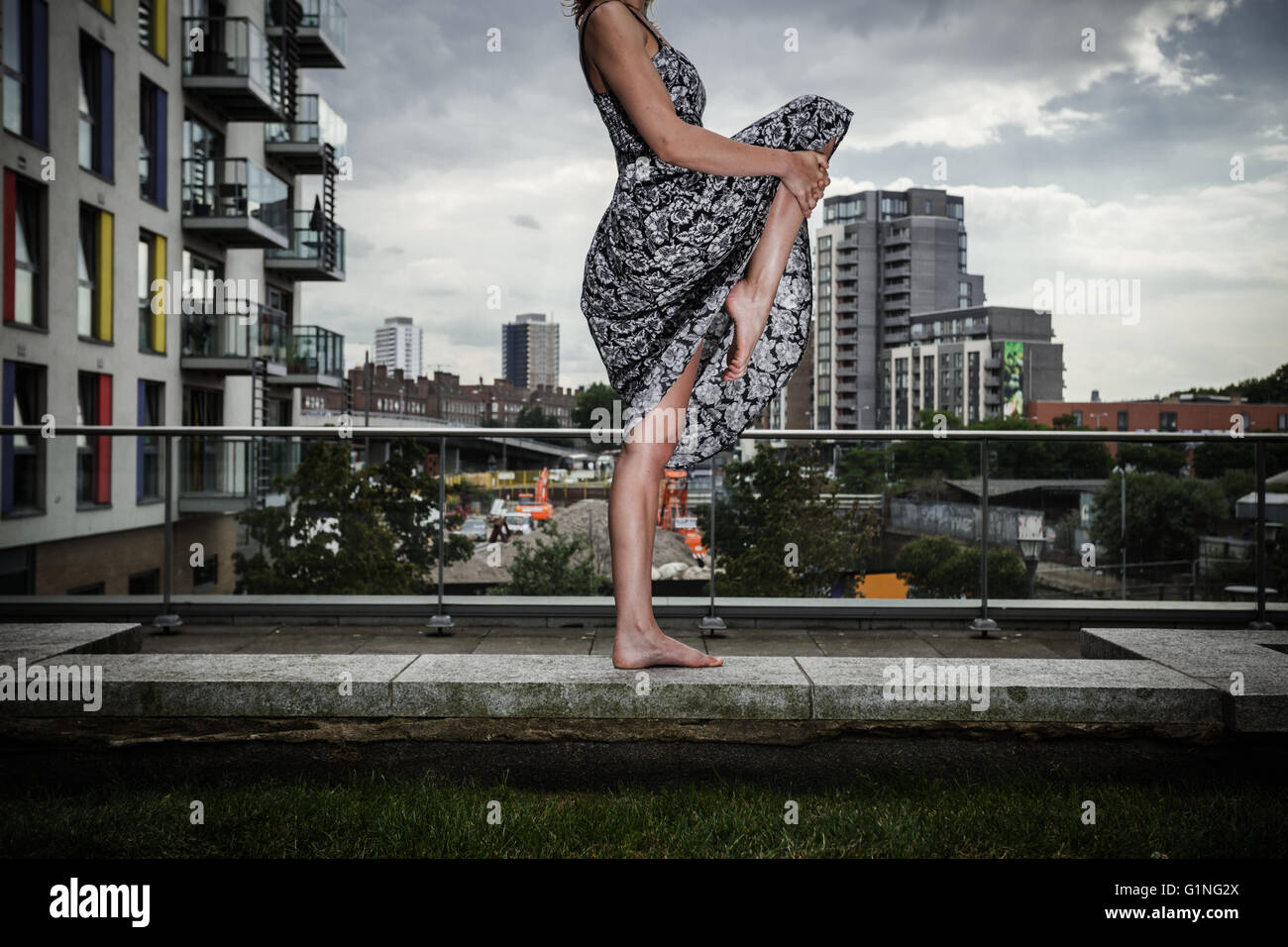 A young woman wearing a dress is raising her leg as she is standing on a roof top - Stock Image