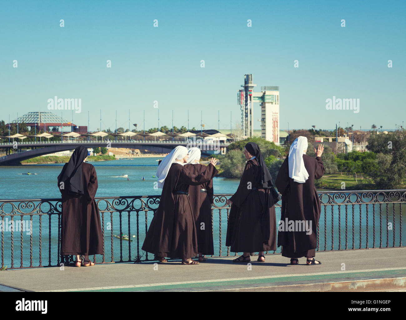 Group of five nuns watching the rowing boats on Guadalquivir river from Puente de Isabel II bridge, Seville, Spain - Stock Image