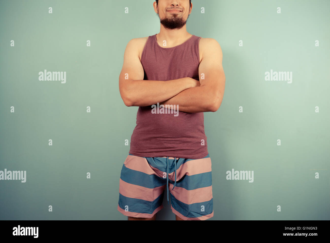 A young man wearing striped shorts and a vest is standing with his arms crossed - Stock Image