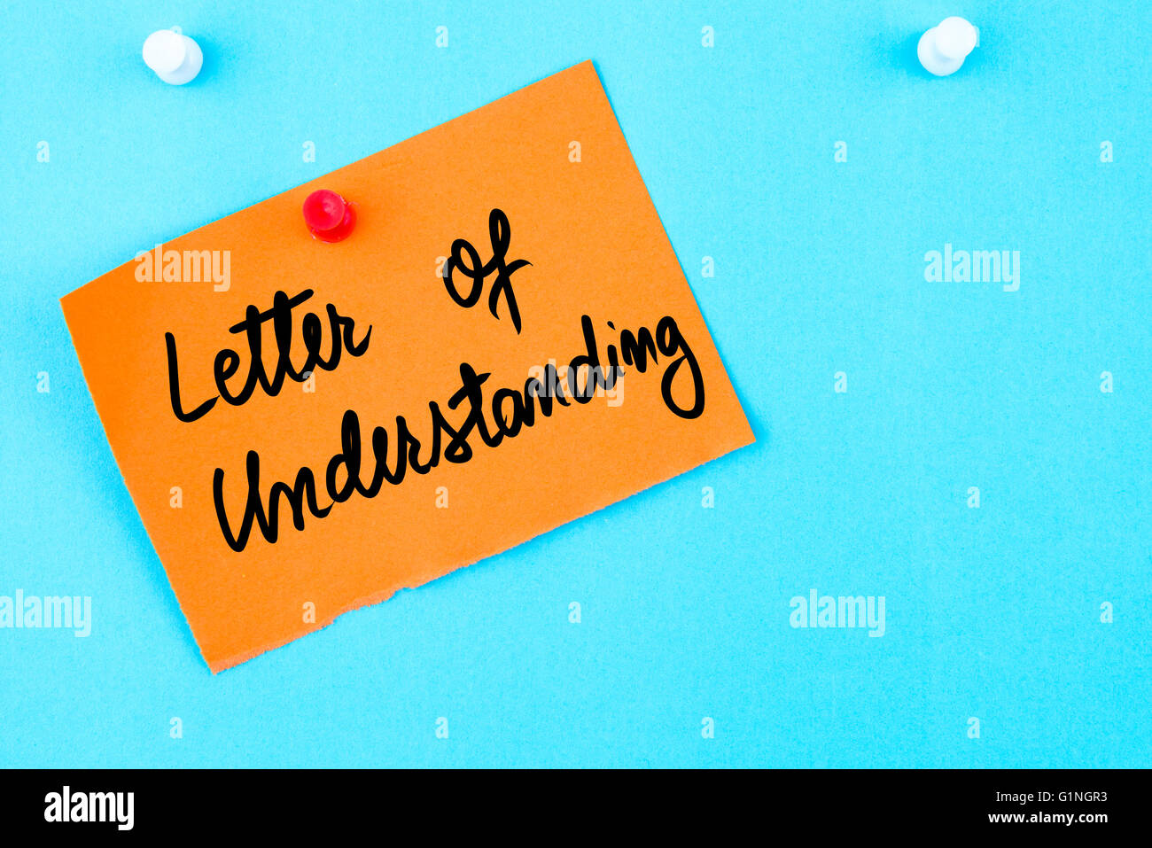 Letter Of Understanding written on orange paper note pinned on cork board with white thumbtack, copy space available - Stock Image
