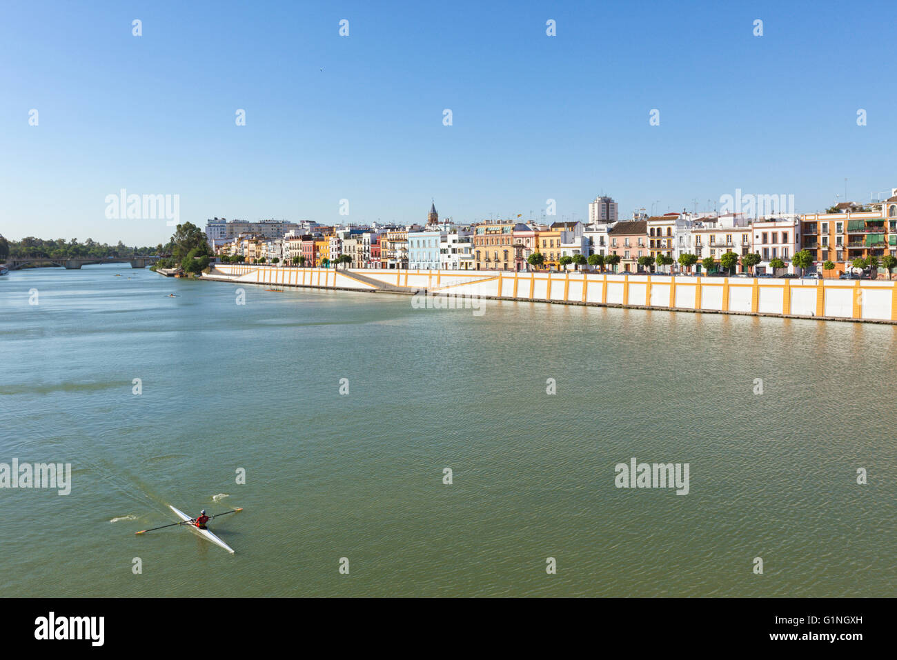 Waterfront of Triana neighborhood on Guadalquivir river, Seville, Spain. Rowing boat in foreground. - Stock Image