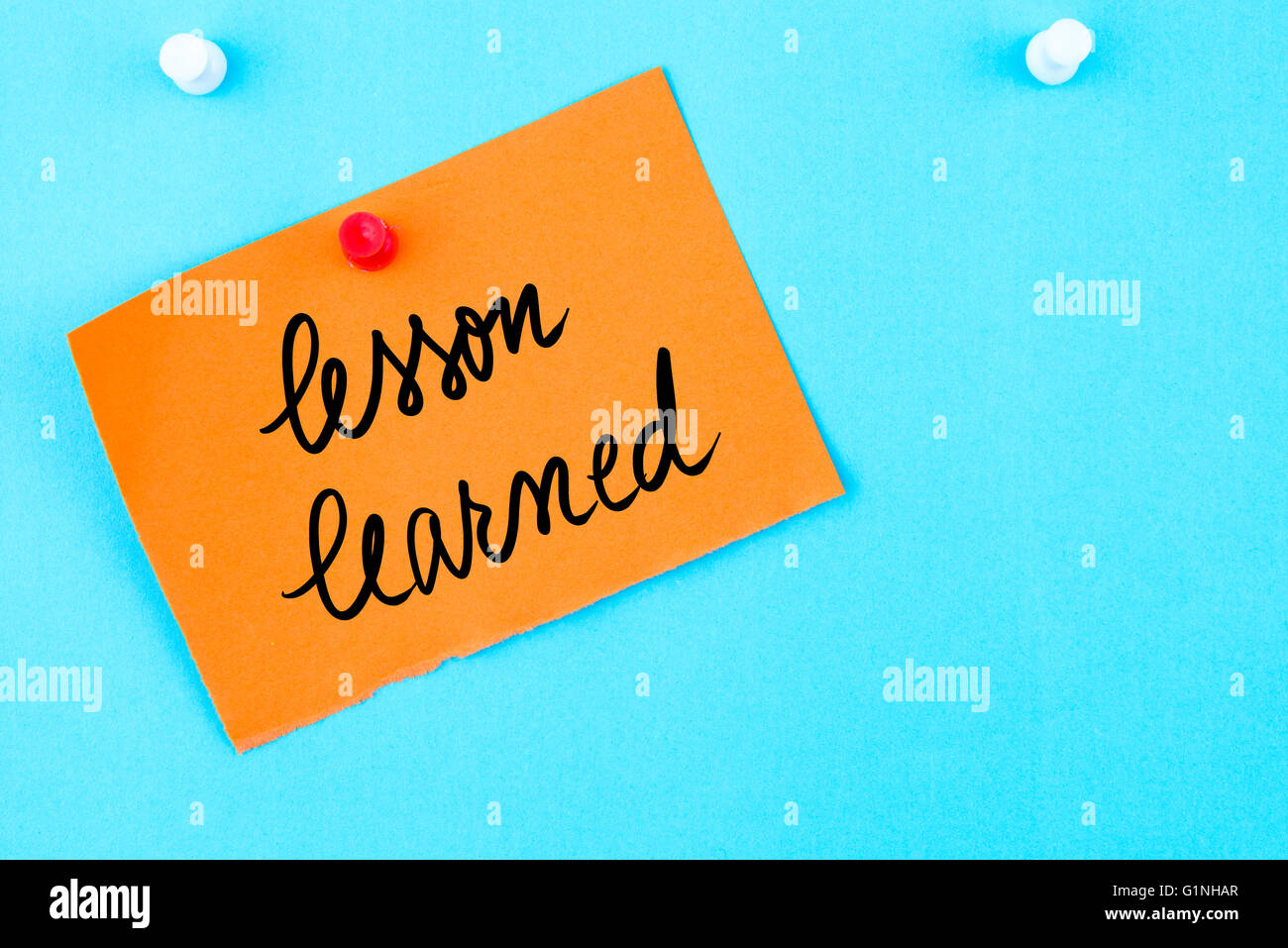 Lesson Learned written on orange paper note pinned on cork board with white thumbtack, copy space available - Stock Image