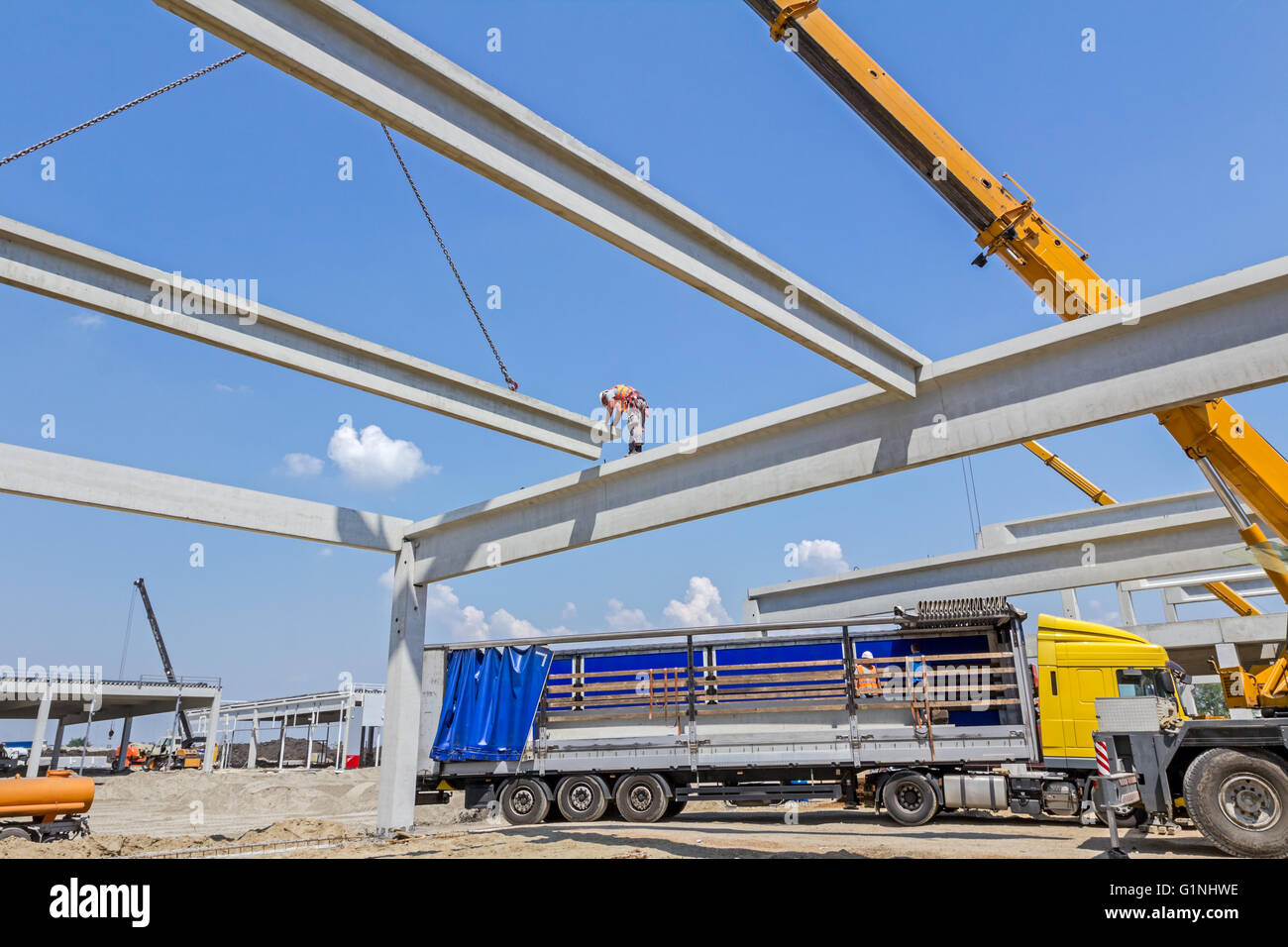 Mobile crane is carry concrete joist to assembly huge hall. - Stock Image
