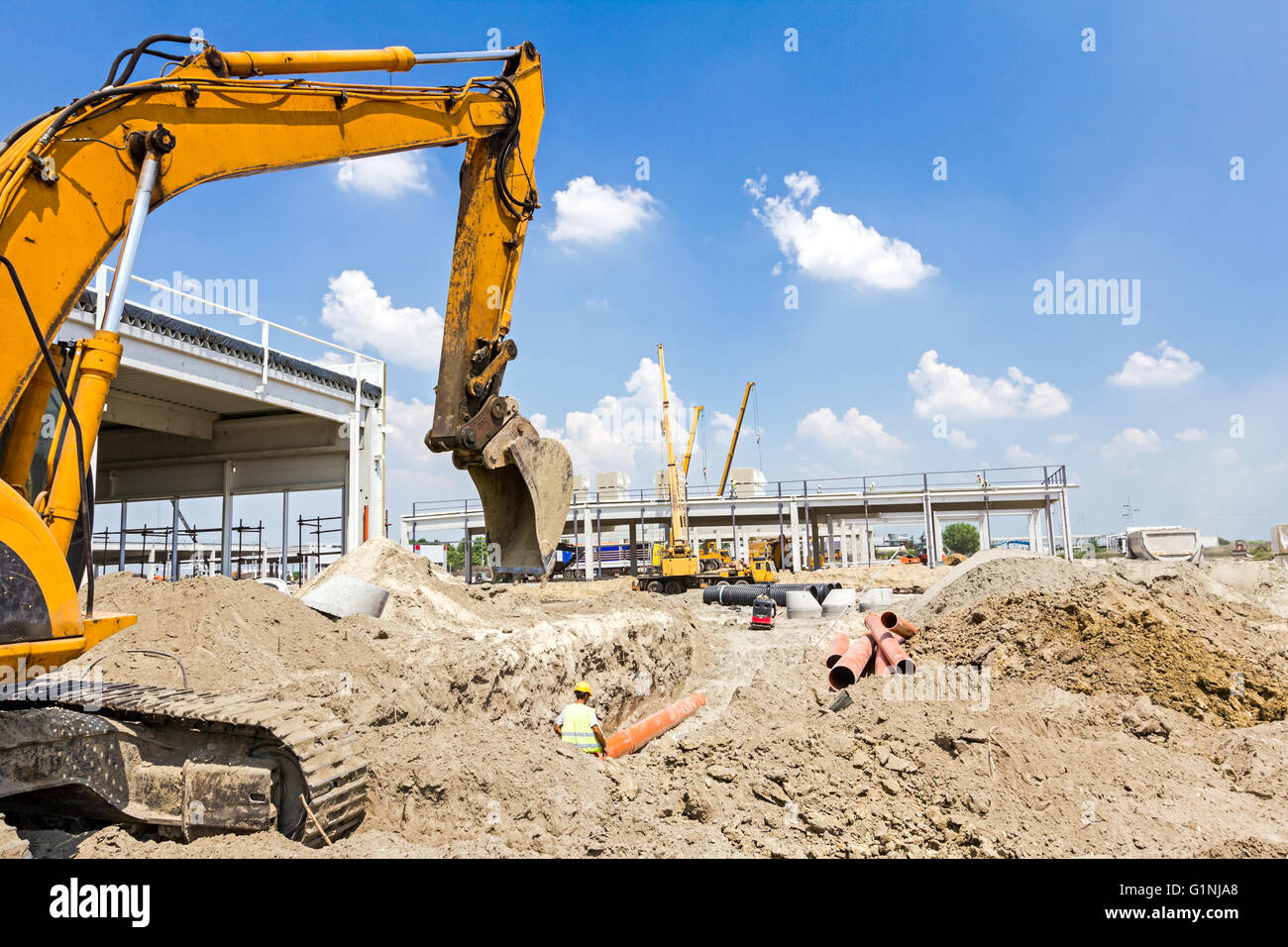 Landscape transform into urban area with machinery, people are working. View on construction site. - Stock Image