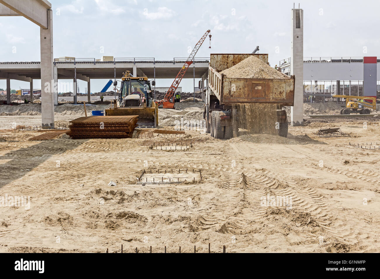 Dumper truck is unloading soil or sand at construction site. Landscape transform into urban area. - Stock Image