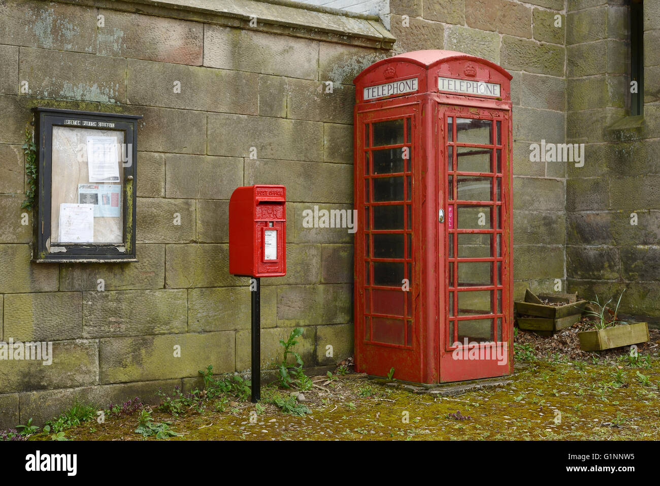 A red post box and red telephone box in the centre of Harthill village in Cheshire UK - Stock Image