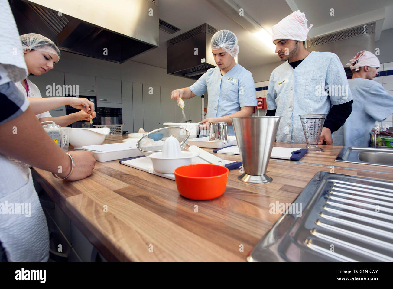 International school class learns how to cook and bake in the training kitchen. - Stock Image