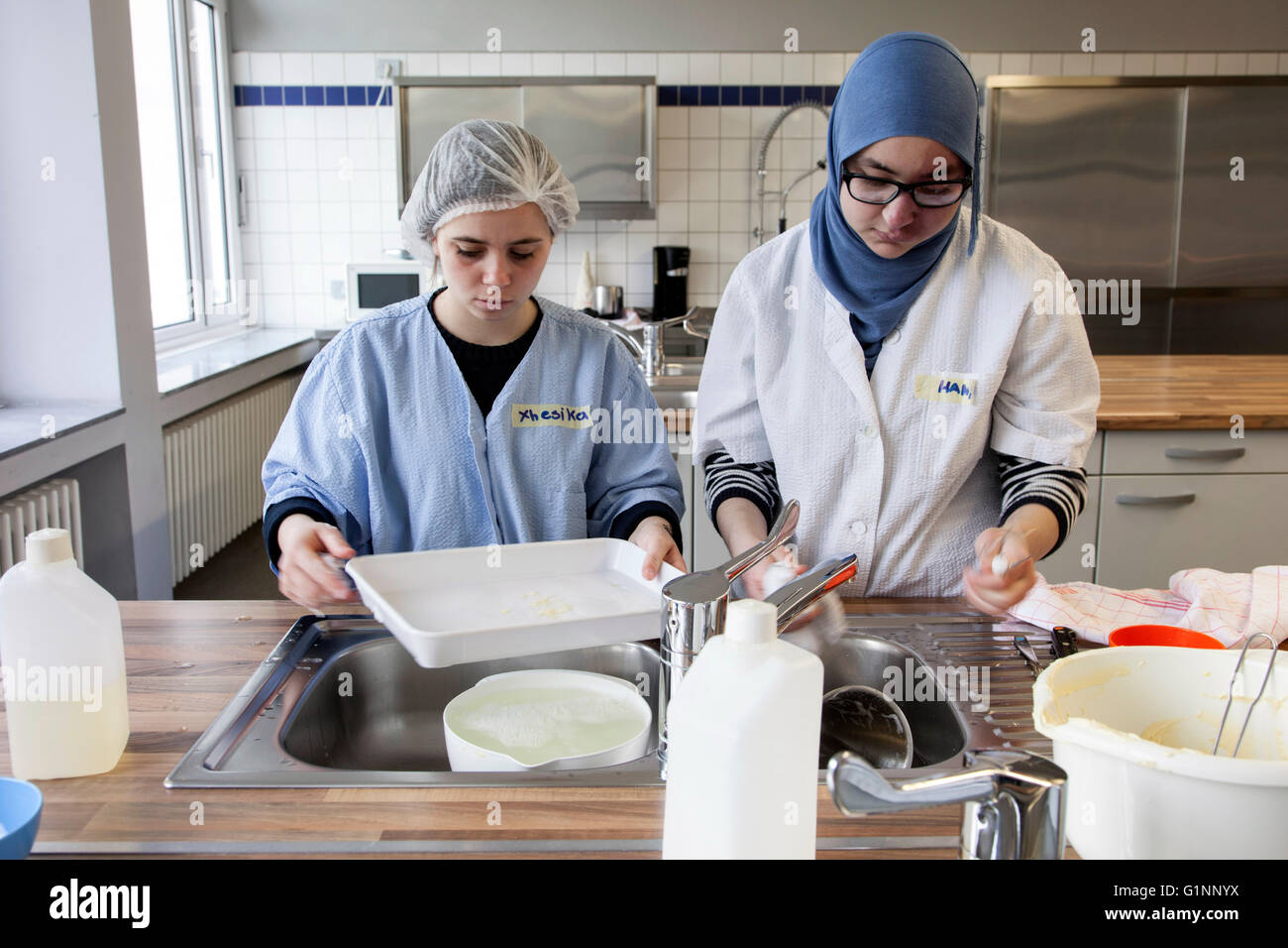 International class during baking a cake in the school kitchen. The trainees wash the kitchen utensils. - Stock Image