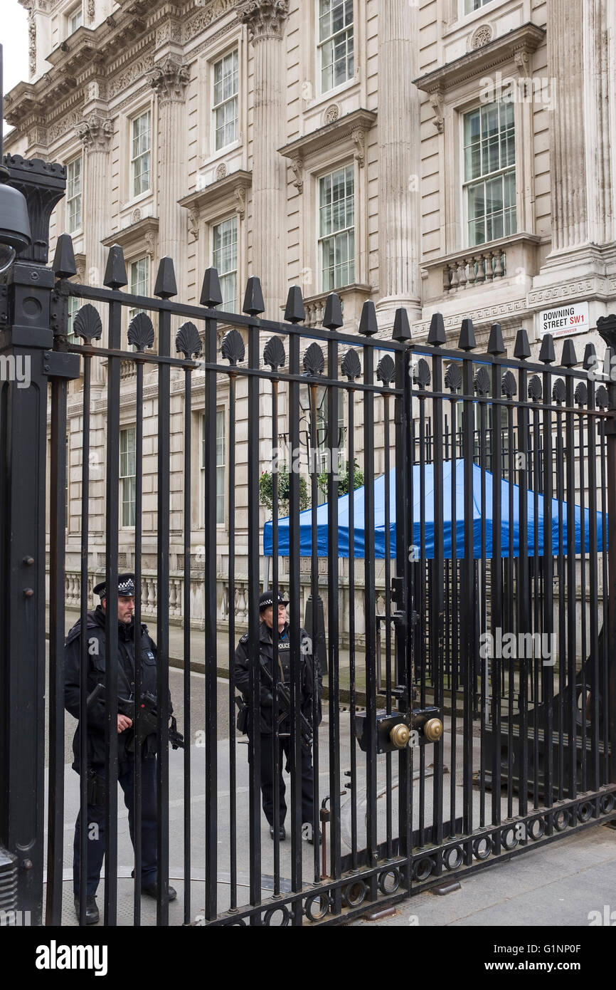 Armed police stand behind security gates at the entrance to Downing Street, London UK - Stock Image