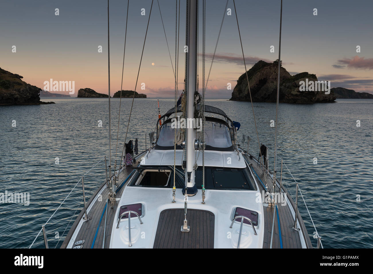 Early morning light and a full moon, yacht at anchor on its own among some of the small islands in the Hauraki Gulf, - Stock Image