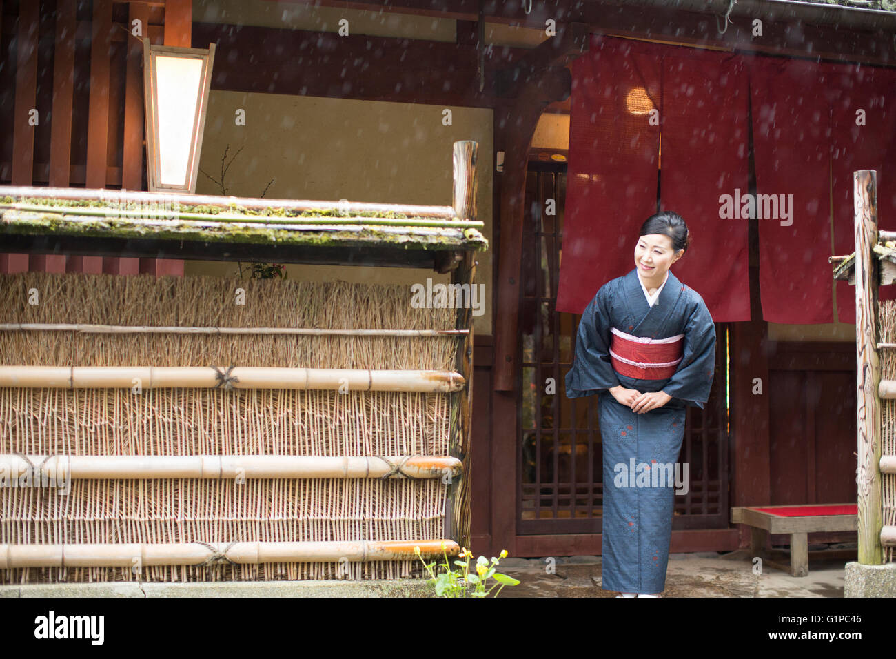 Mid Adult Japanese woman in kimono bowing - Stock Image