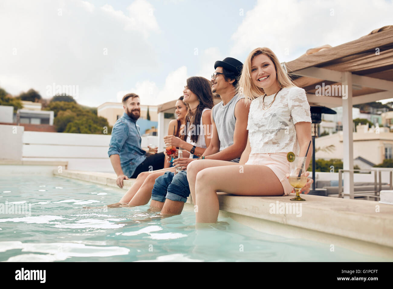 Portrait of happy young woman sitting by the pool with her friends partying. Young people relaxing by the swimming - Stock Image