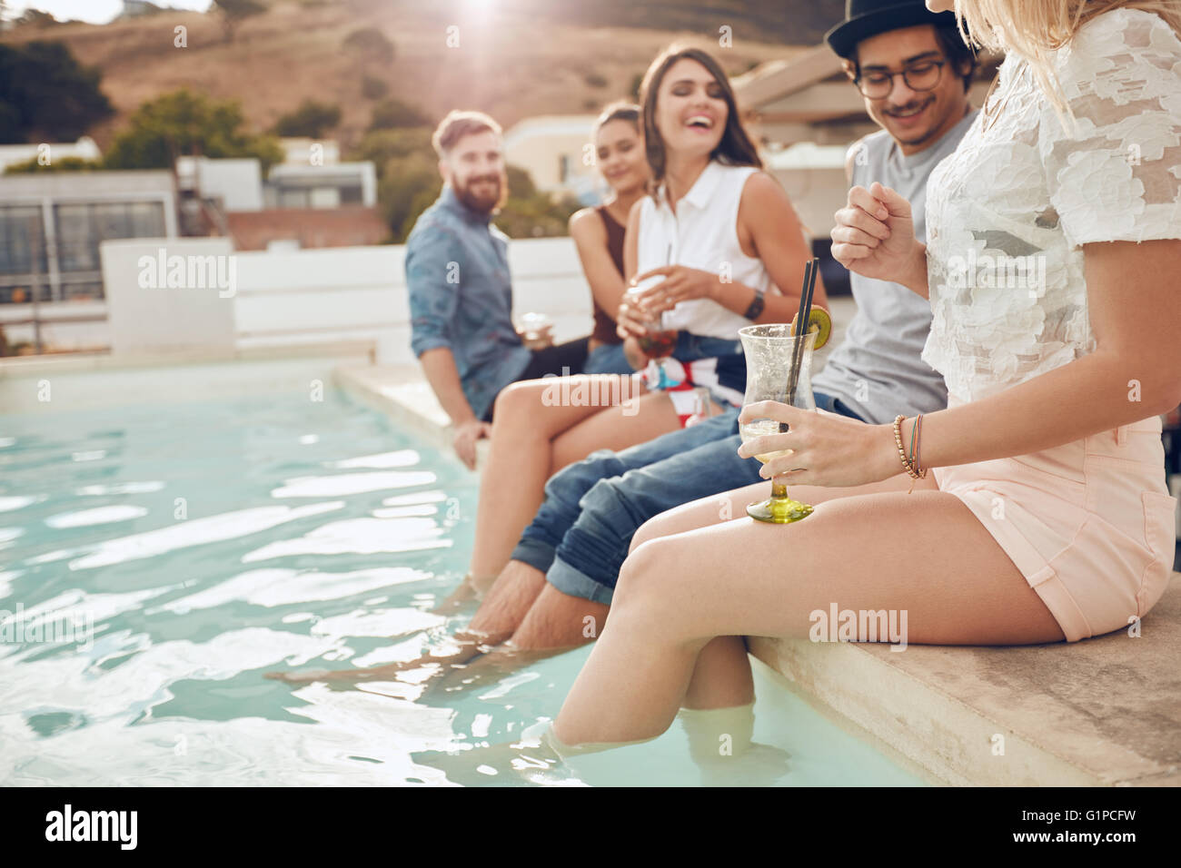 Shot of young people drinking cocktails the swimming pool. Friends sitting on the edge of the pool with feet in - Stock Image