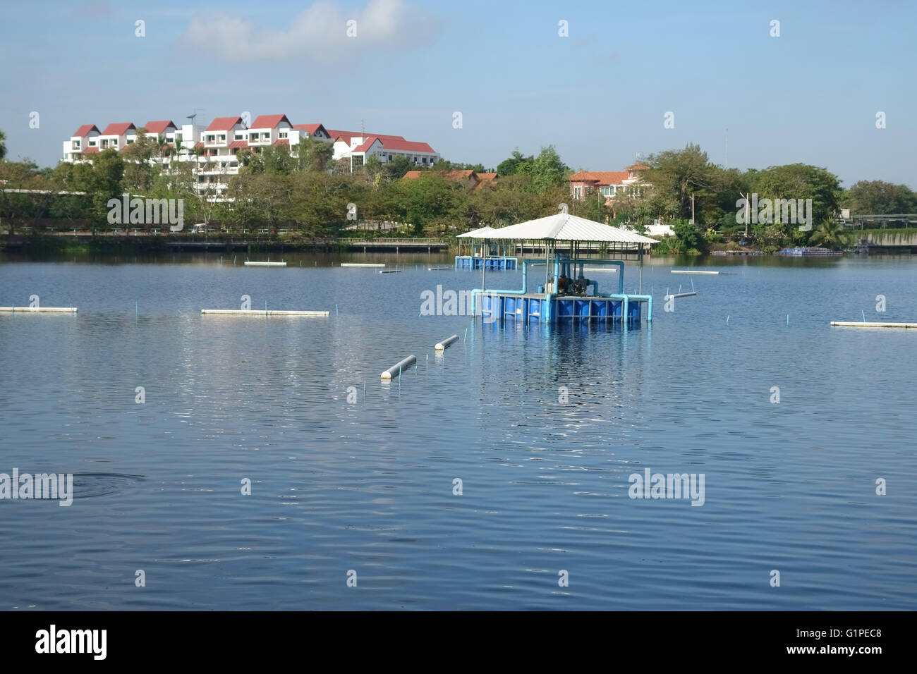 Lake with irrigation pumps to circulate water and irrigate surrounding gardens, Bangkok, Thailand - Stock Image