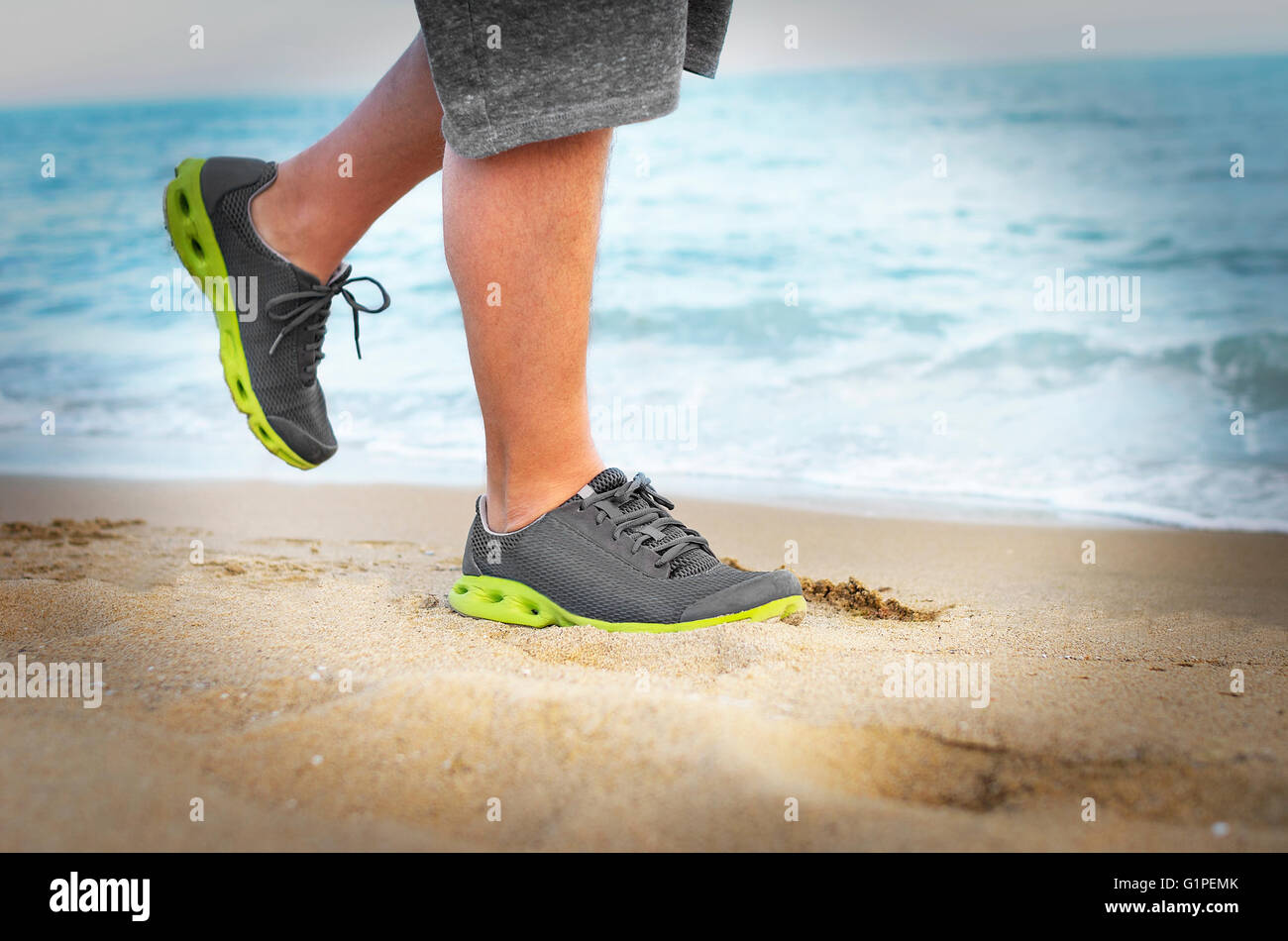 Men's feet in sneakers go on the beach. Close-up. Toned photo. - Stock Image