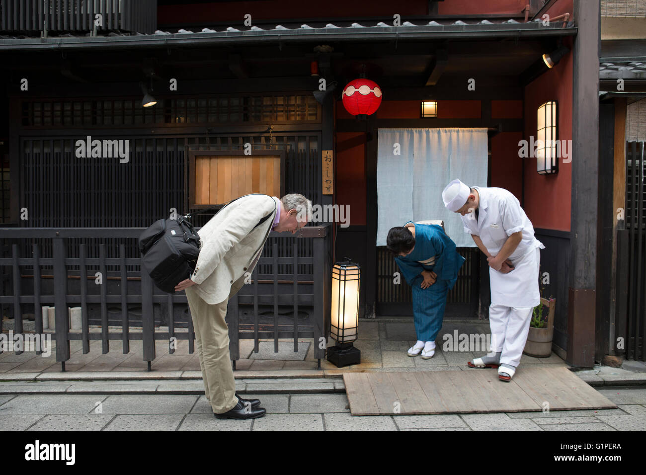 Senior Japanese hostess, cook and Caucasian man bowing - Stock Image