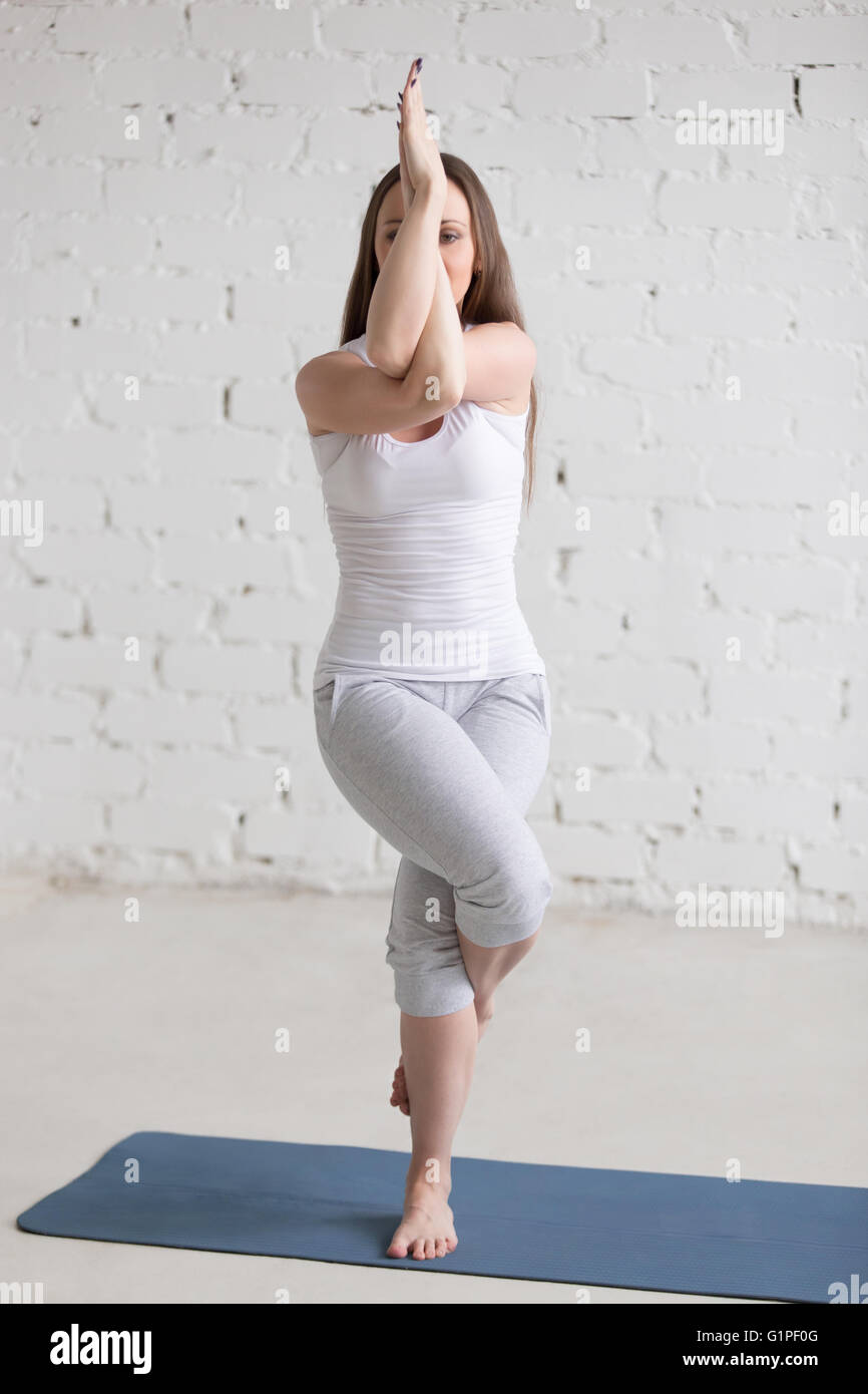 Attractive young woman working out indoors. Beautiful model doing exercises on blue mat in room with white walls. - Stock Image