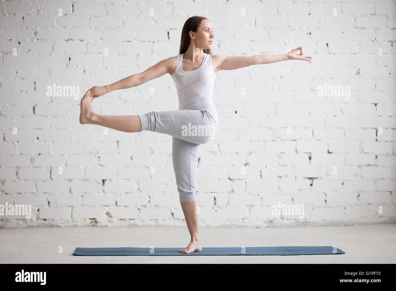 Attractive young woman working out indoors. Beautiful model doing exercises on blue mat in room with white walls - Stock Image