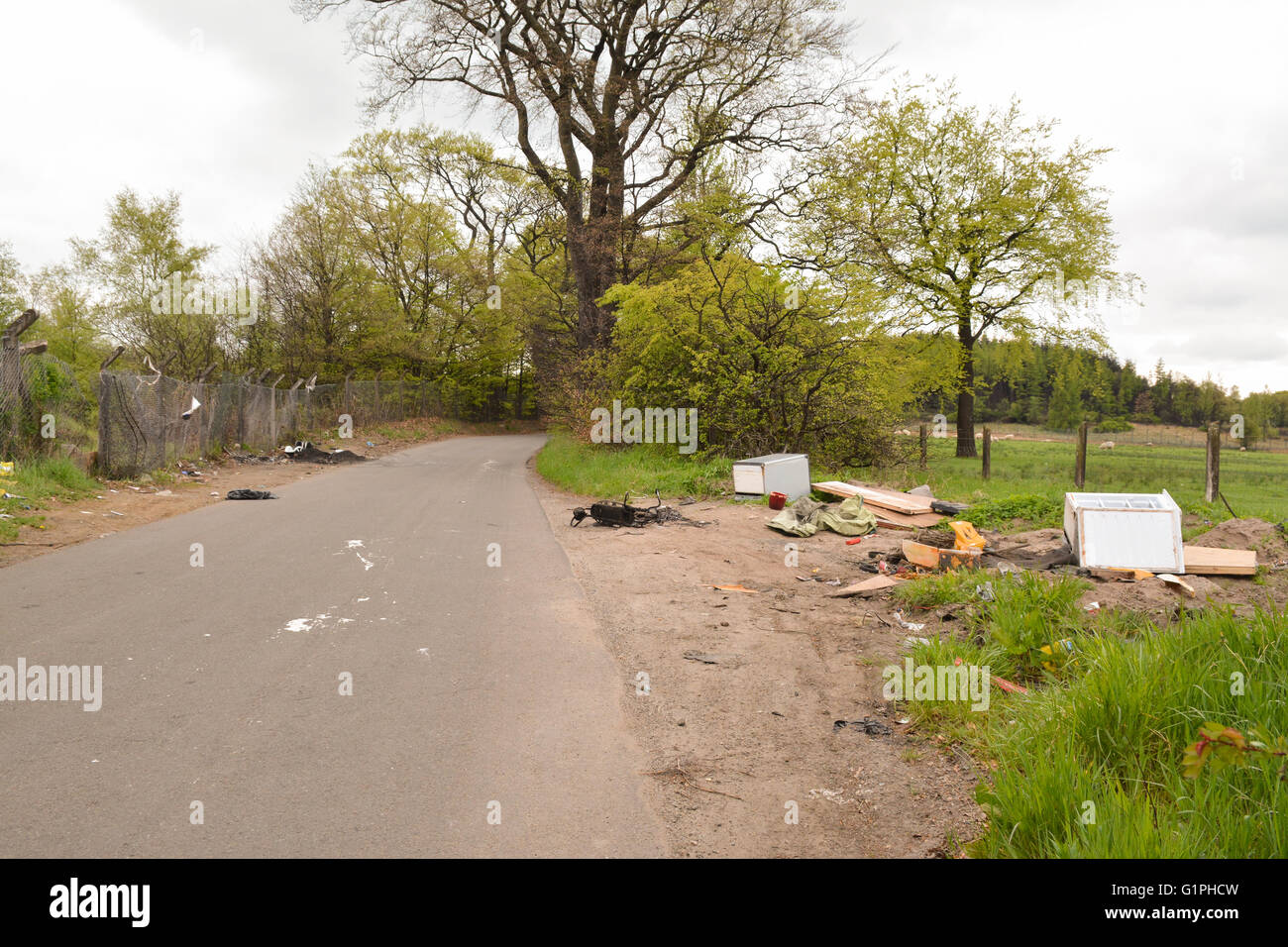 fly tipping, including electrical appliances, by the side of a rural road in Plains, Airdrie, North Lanarkshire, - Stock Image