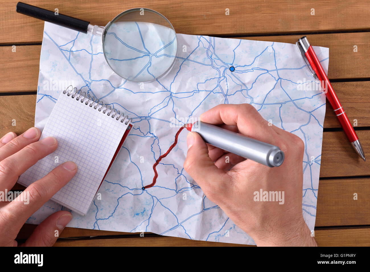 hands tracing a path on map on a wooden table. With pen notepad and magnifying glass. Top view - Stock Image