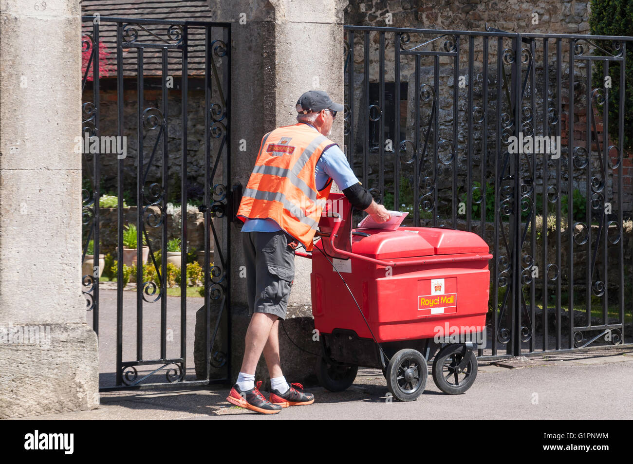 Royal Mail postman doing his rounds with postal cart, High Street, Thame, Oxfordshire, England, United Kingdom - Stock Image