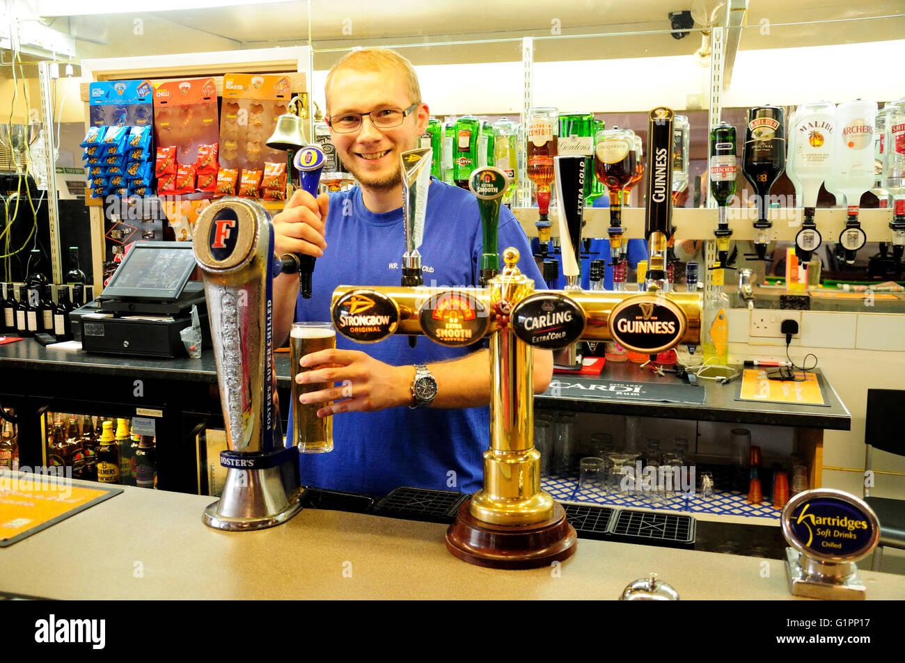 Barman serving beer at bar, WR Sports Club, Woodthorpe Road, Ashford, Surrey, England, United Kingdom - Stock Image