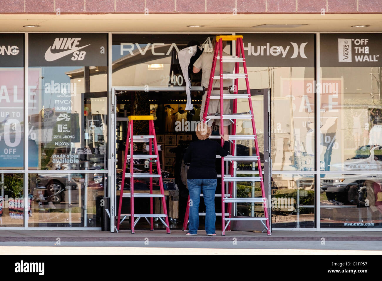 A Caucasian Woman Steadies A Ladder While A Man Strips A Sign From A Stock Photo Alamy