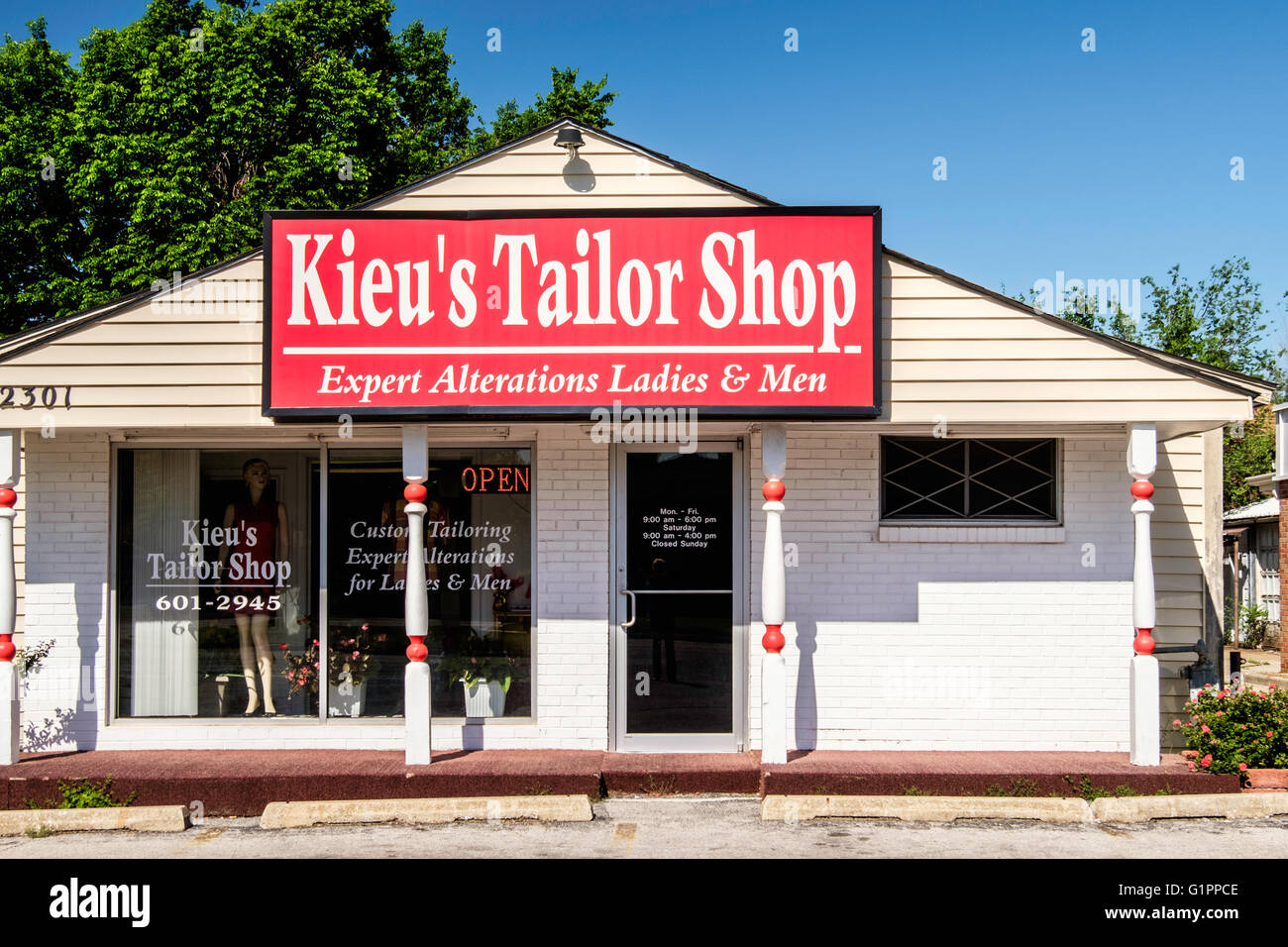 The exterior of a small tailor shop inside a remodeled former home. - Stock Image
