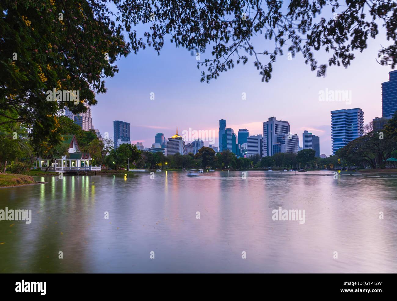 Sunset view of Bangkok skyline in Lumpini public park, Bangkok, Thailand - Stock Image