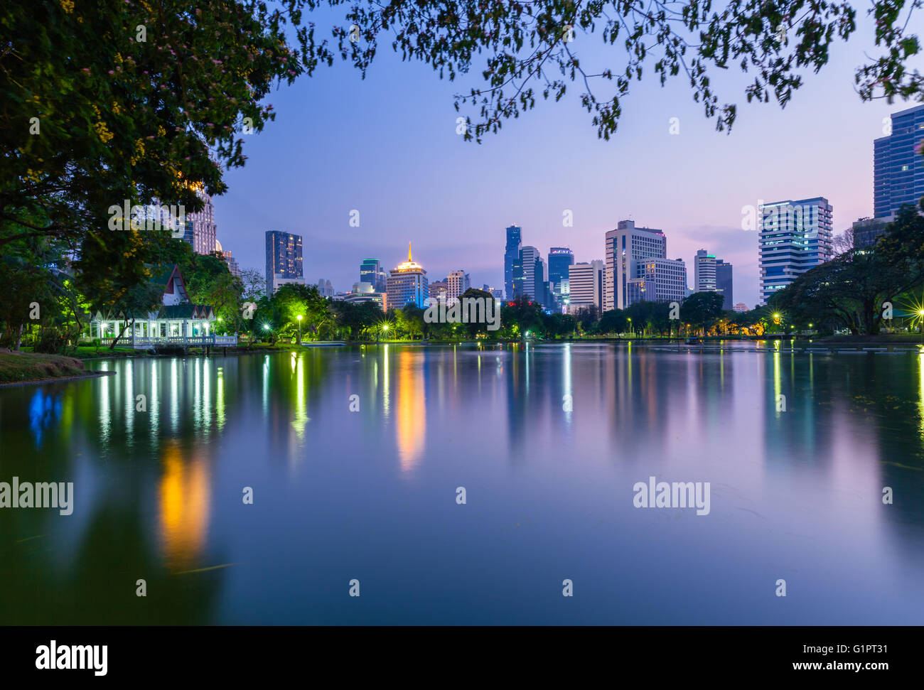Dusk view of the city skyline in Lumpini public park, Bangkok, Thailand - Stock Image