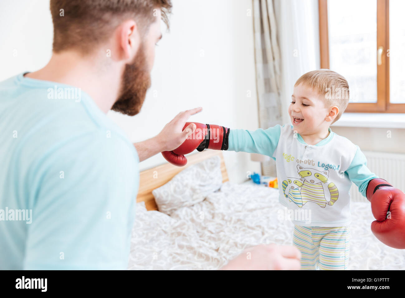 Bearded young father playing with his little son in boxing gloves at home Stock Photo