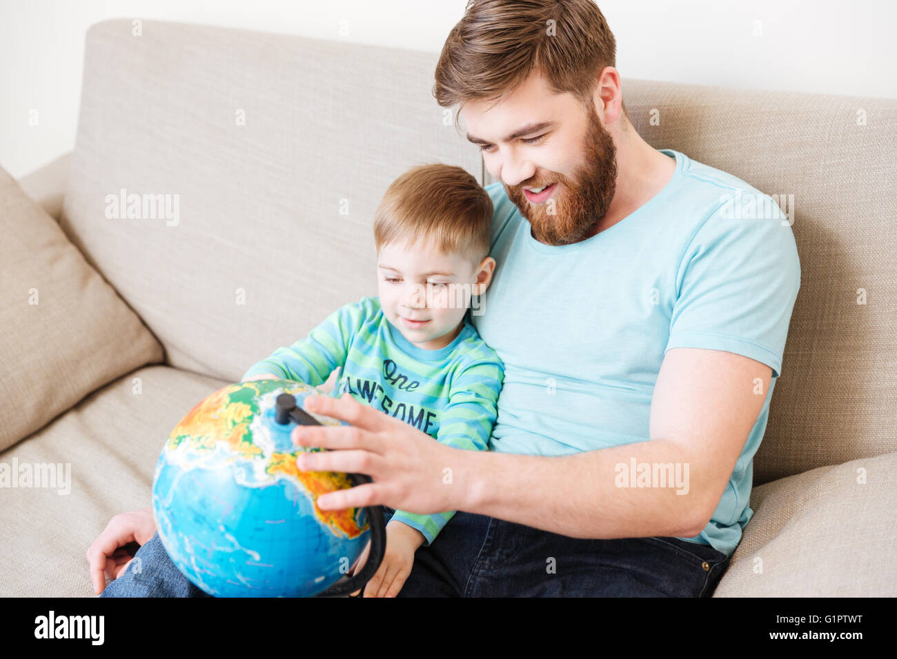 Happy dad and son sitting and looking at globe together at home - Stock Image
