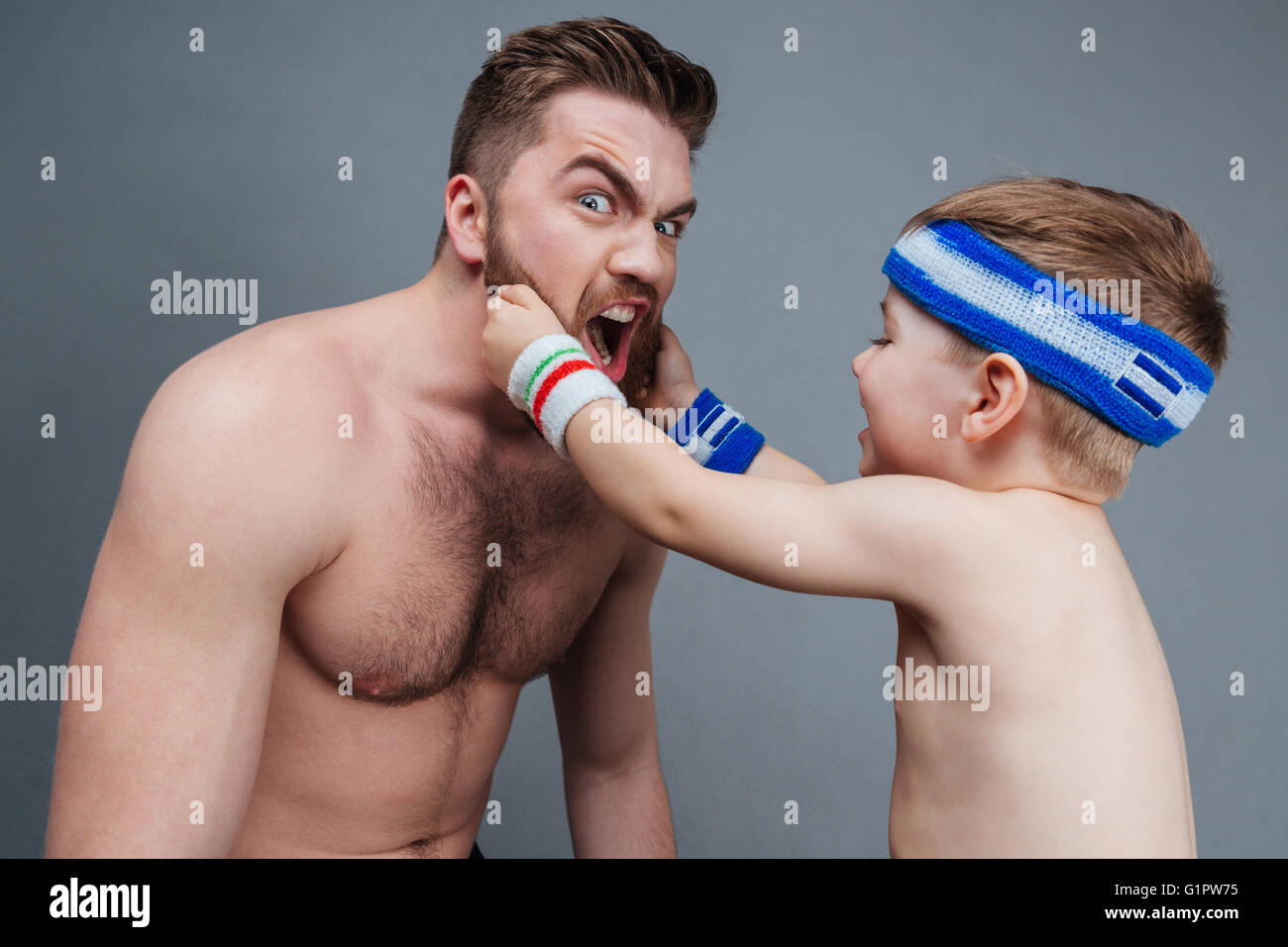 Smiling little son playing with dad beard over grey background Stock Photo