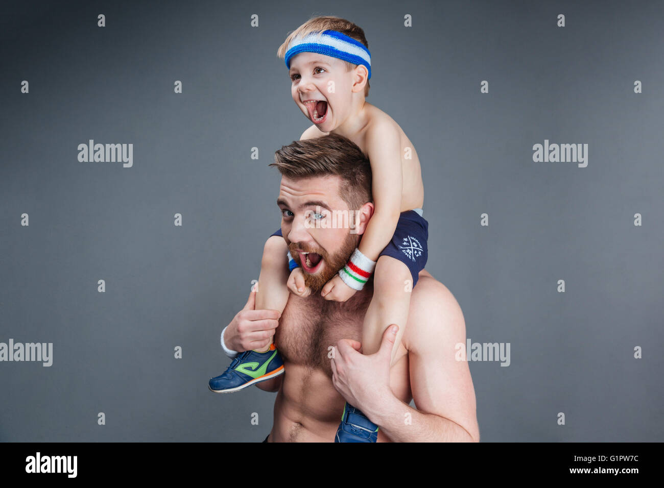Closeup of father and his little son having fun and shouting over grey background Stock Photo