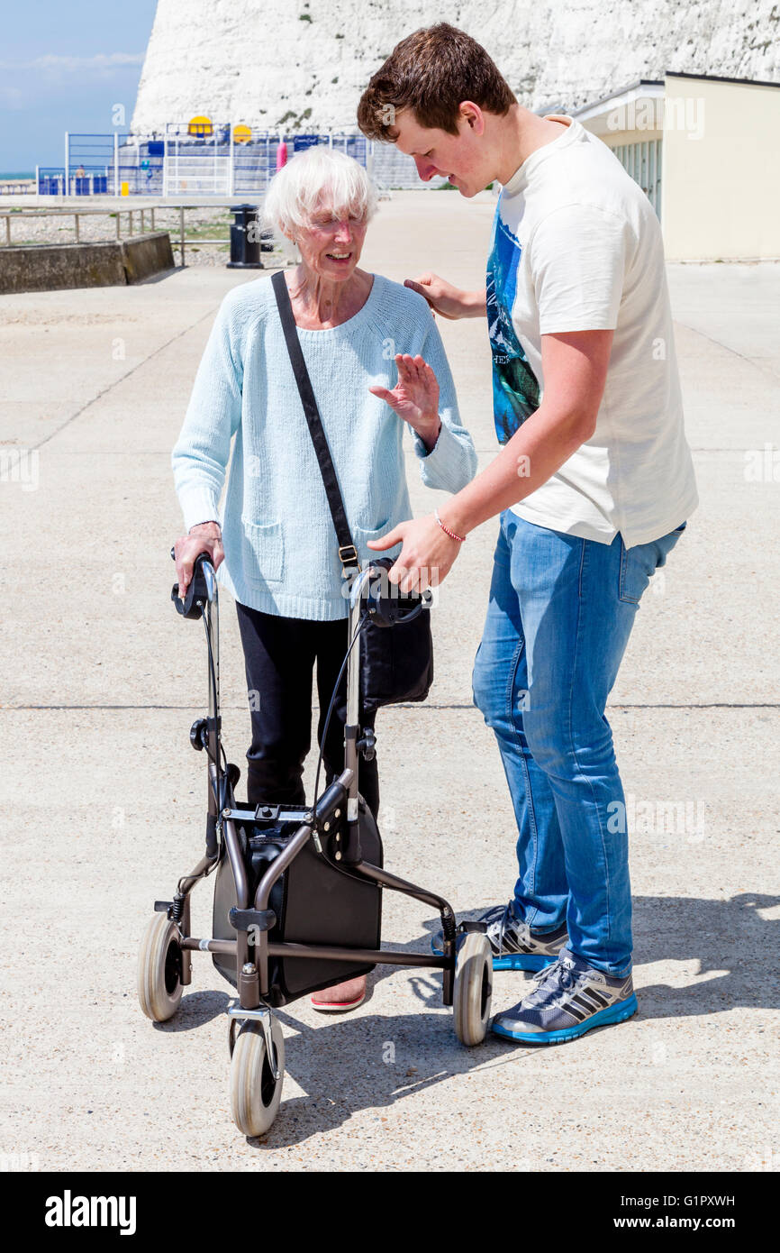 An Elderly Disabled Woman Using A Rollator Walking Aid Helped By Her Grandson, Brighton, Sussex, UK - Stock Image