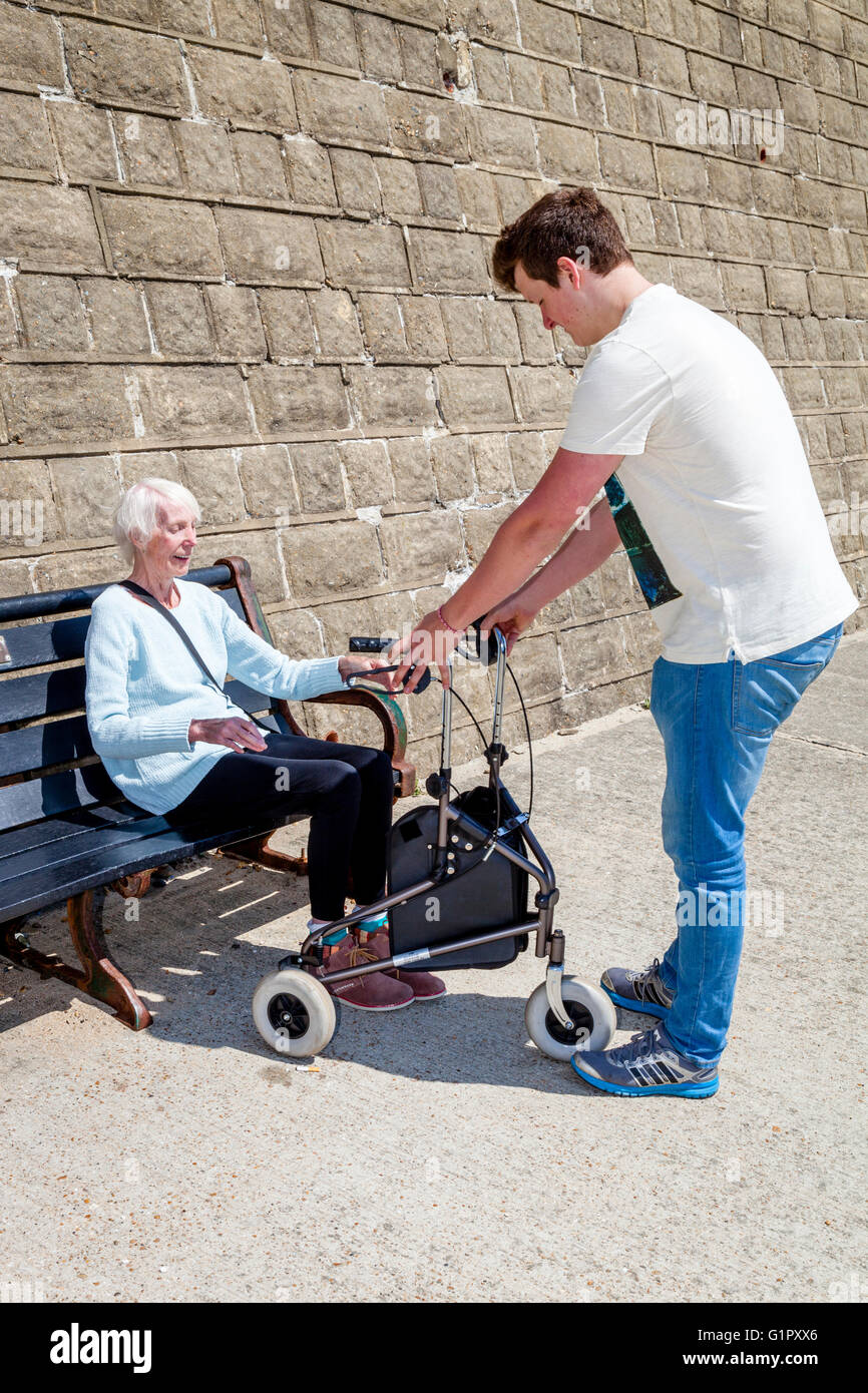 An Elderly Disabled Woman Getting Up From A Bench, Helped By Her Grandson, Brighton, Sussex, UK - Stock Image
