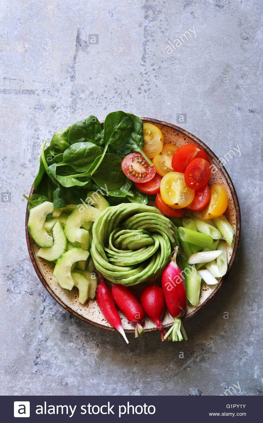 Spring salad bowl with spinach,cherry tomato,cucumber,spring onion,radishes and avocado rose.Top view. - Stock Image