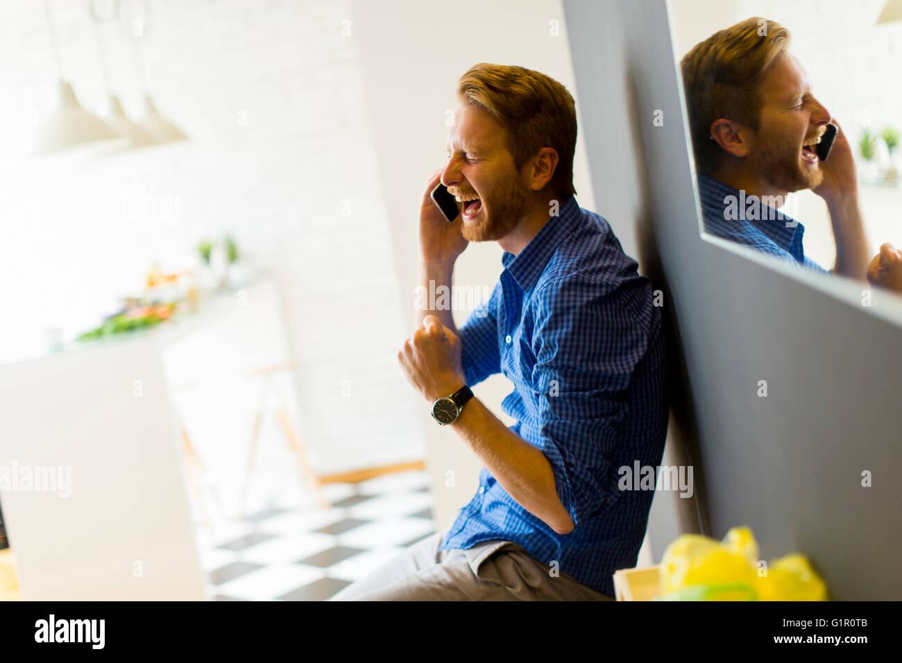 Man on the phone yelling with joy - Stock Image