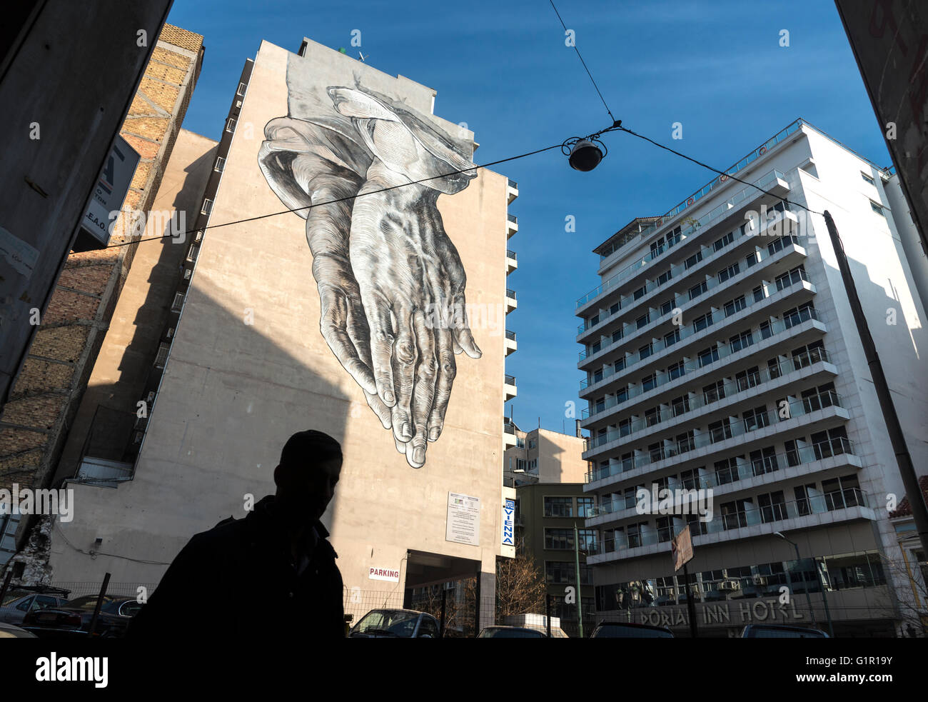 A street art mural in the form of a giant pair of praying hands looms over Pireos street in the Omonia district - Stock Image