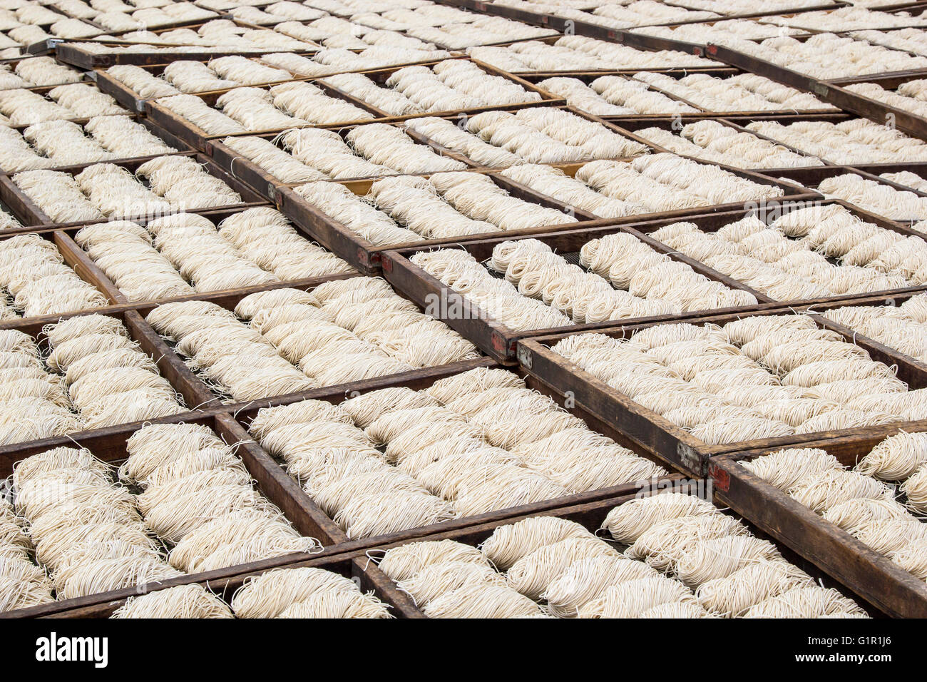Many chinese noodles drying under the sun in wooden trays - Stock Image