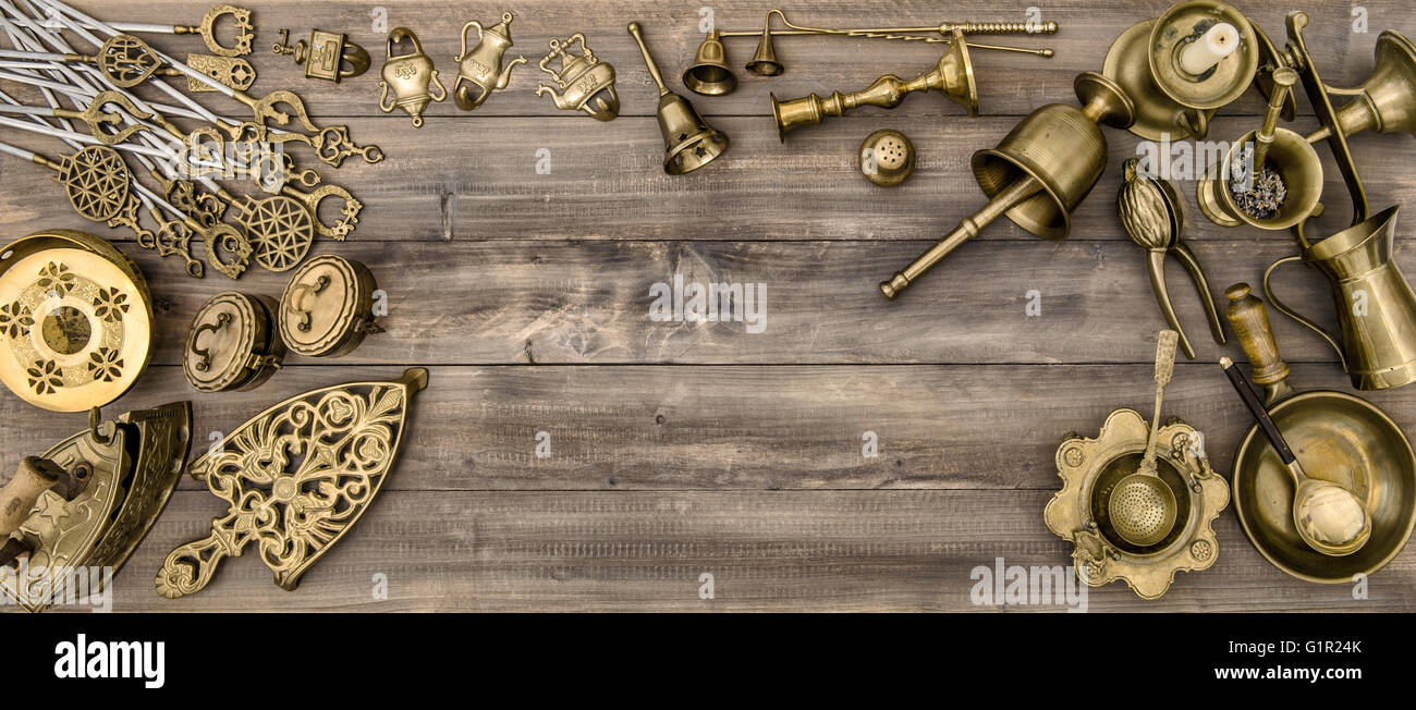 Vintage brass table ware. Kitchen table with antique tolls and utensils - Stock Image