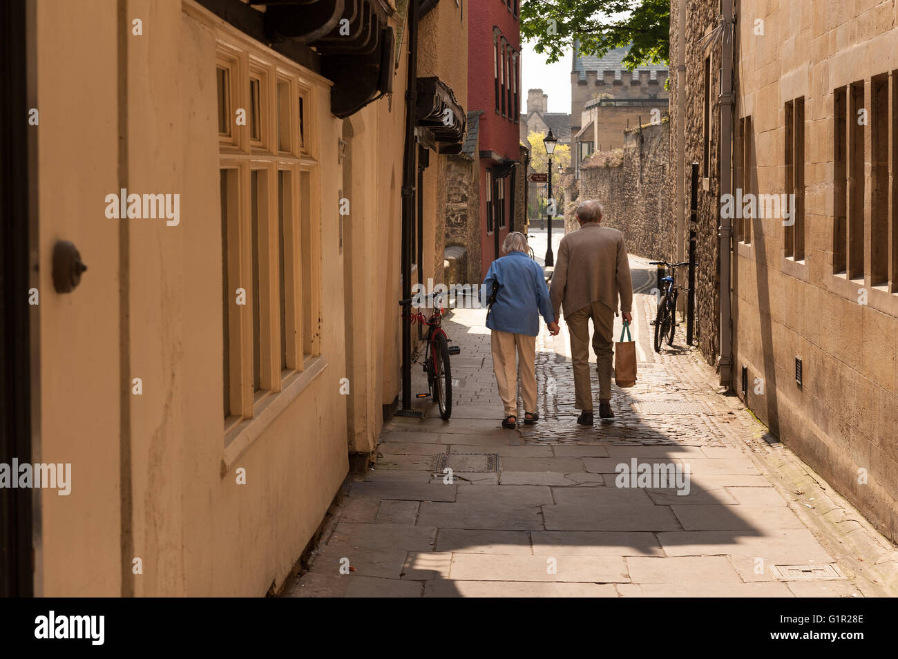 Love never dies two old pensioners walking hand in hand along romantic old Oxford flagstone path - Stock Image