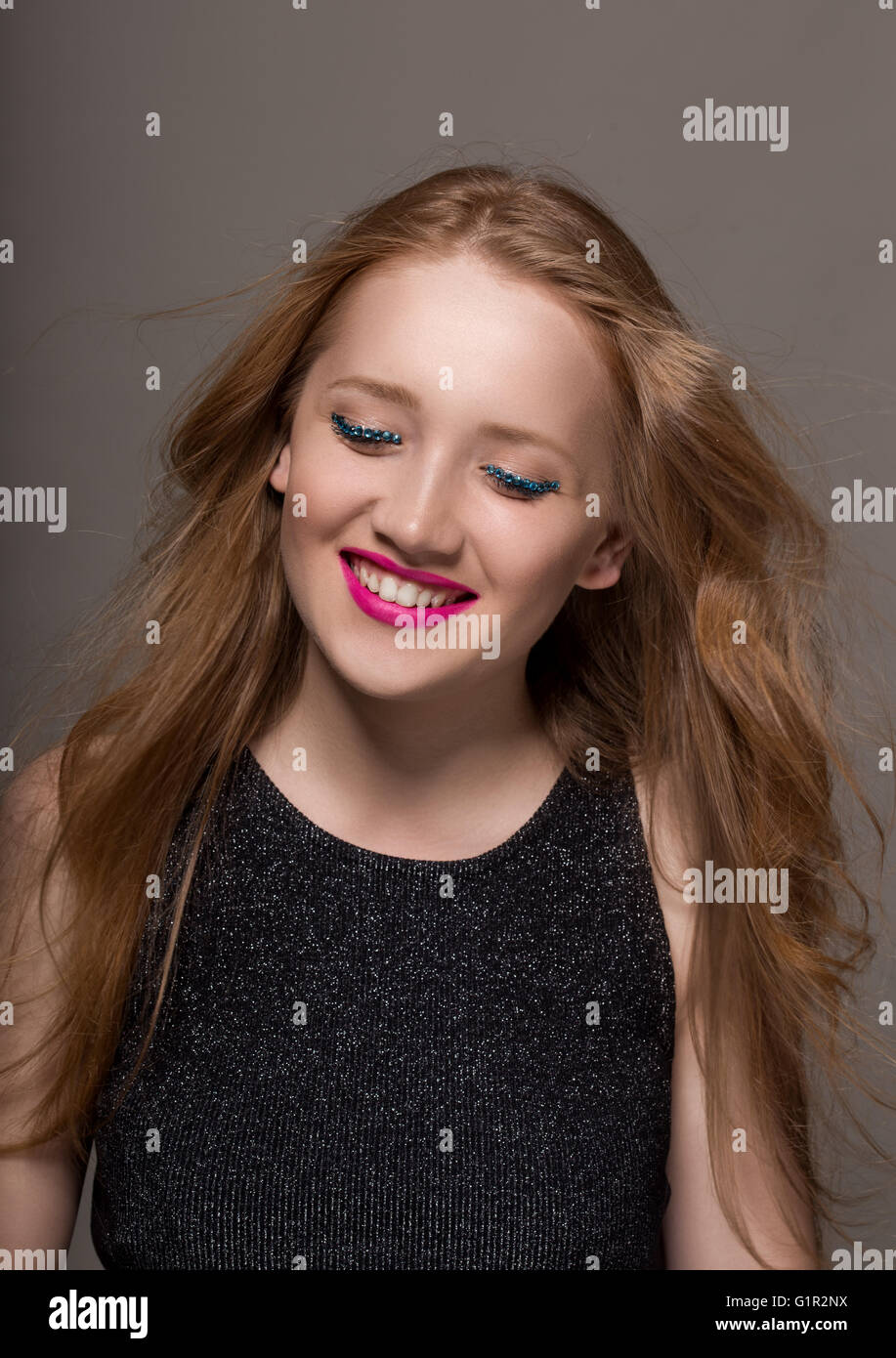 Portrait of a young woman in studio with glittery makeup smiling - Stock Image