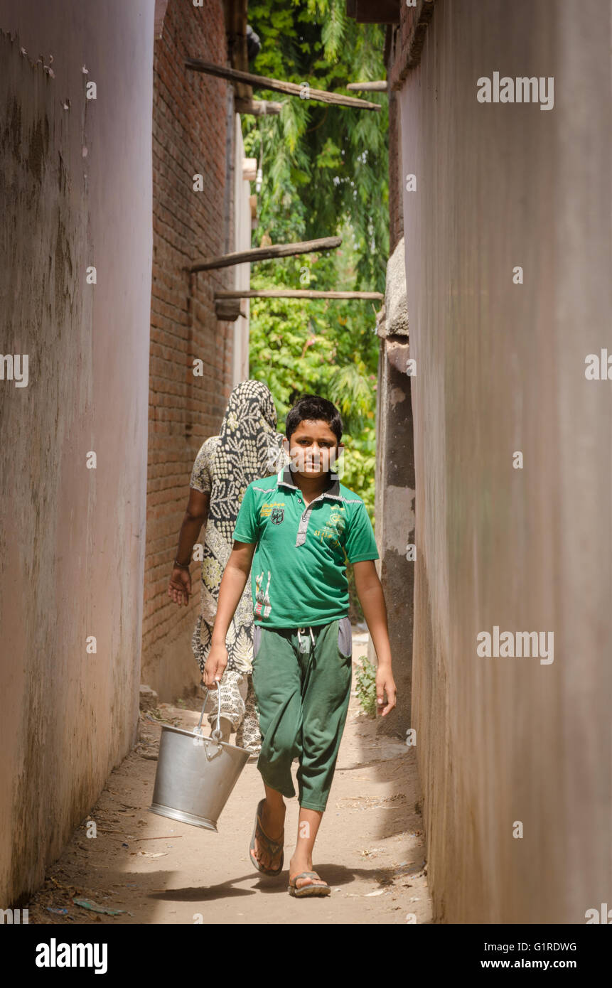 Young boy walks down an alleyway carrying a bucket of water in a village in Gujarat, India - Stock Image