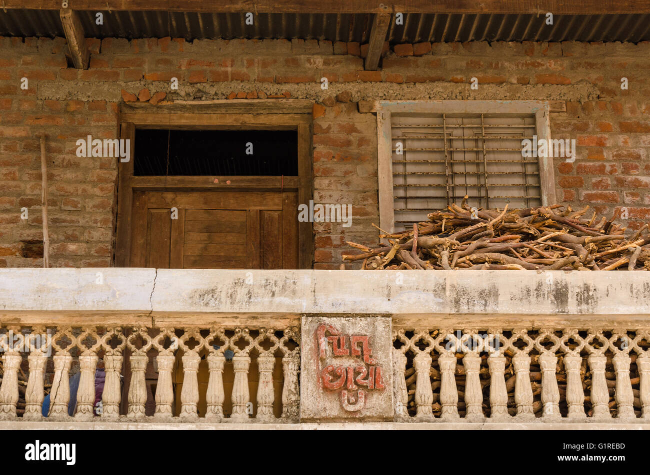 Firewood kept in the balcony of a typical village house in Gujarat, India - Stock Image
