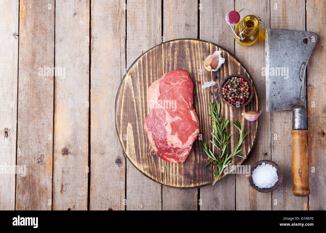 Raw fresh meat Steak with salt and pepper, rosemary and tomatoes on cutting board Copy space. Top view Stock Photo